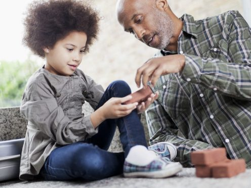 "A man and a small girl playing with ""mini bricks"". Man is wearing a checkered shirt, girl with curly hair sitting next to him."