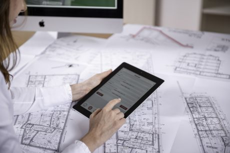 Woman at workplace with blueprint holding tablet computer, Fast Forward Commercial Excellence