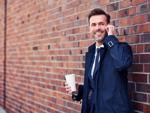 Middle-aged business executive making phone call while enjoying a cup of coffee outside
